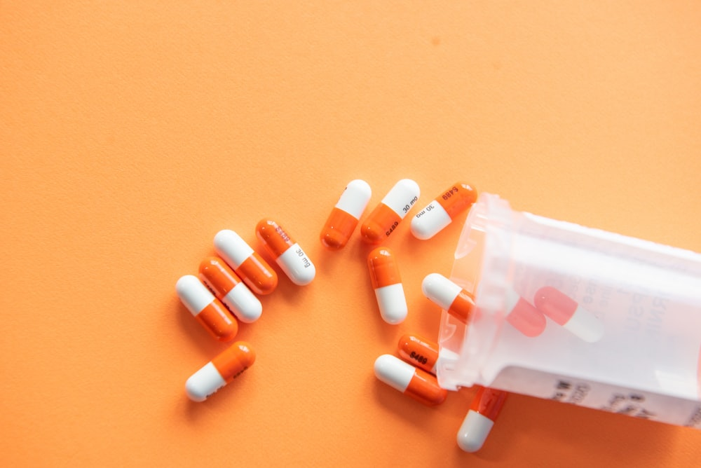 orange and white medication pill