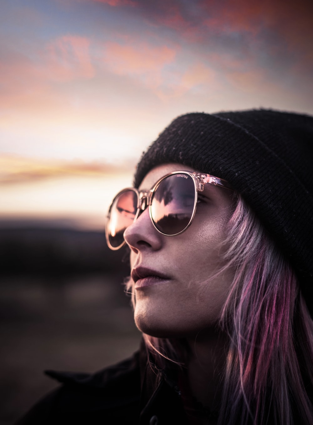 woman wearing black knit cap and silver framed aviator sunglasses