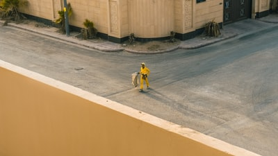 man in yellow shirt riding bicycle on gray concrete road during daytime saudi arabia teams background