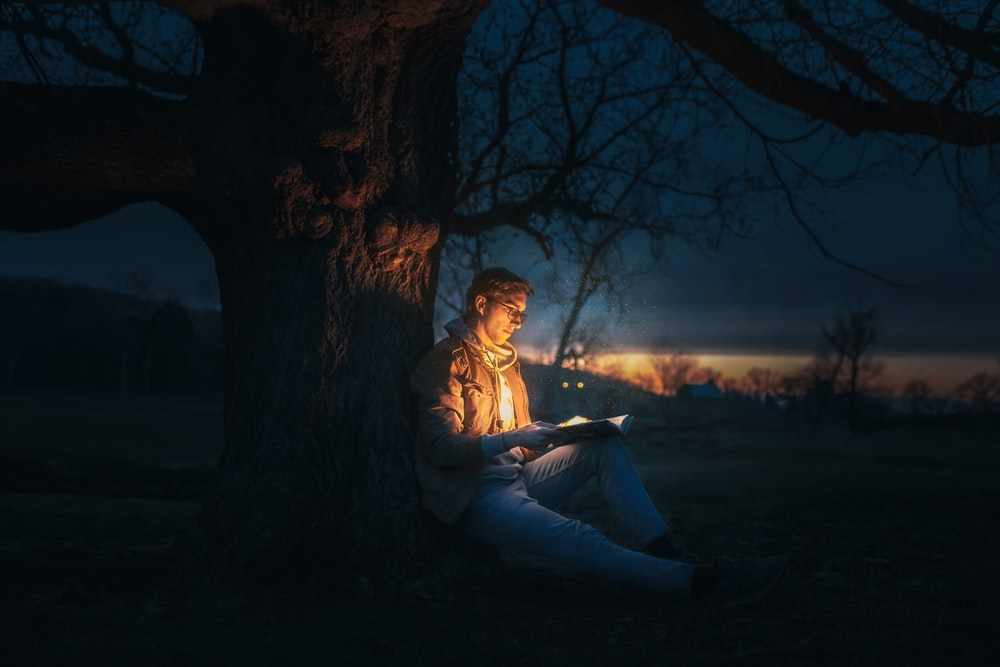 woman in white dress sitting on ground under tree during night time
