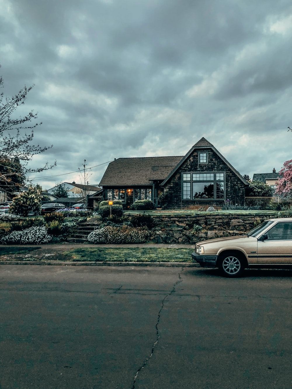 white sedan parked beside brown wooden house under white clouds during daytime