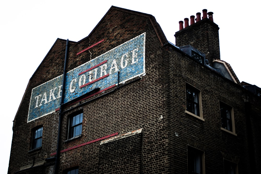 brown brick building with blue and white signage