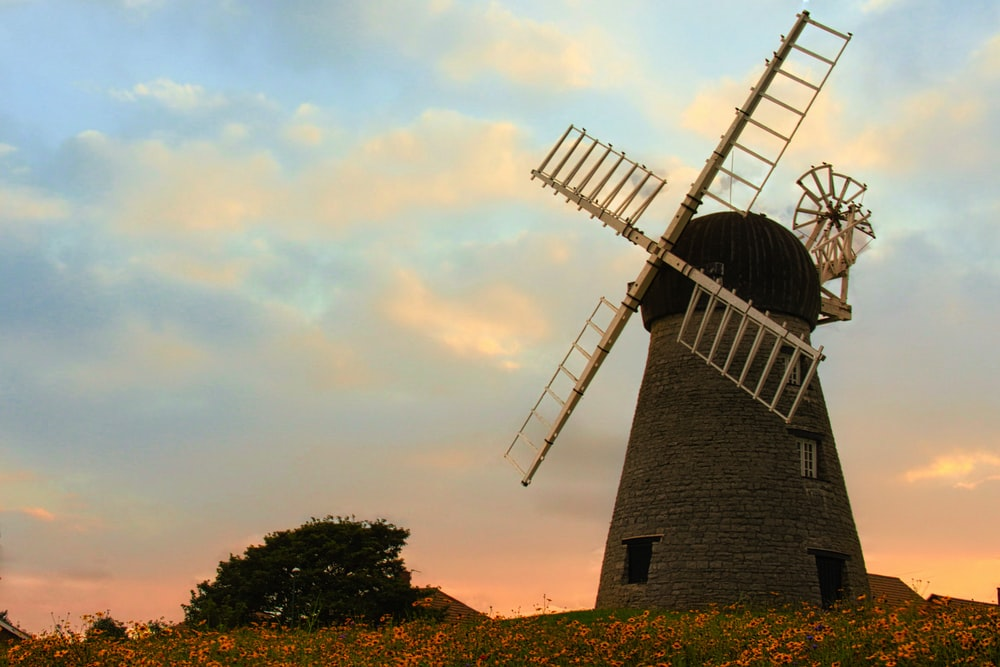 brown windmill under cloudy sky during daytime