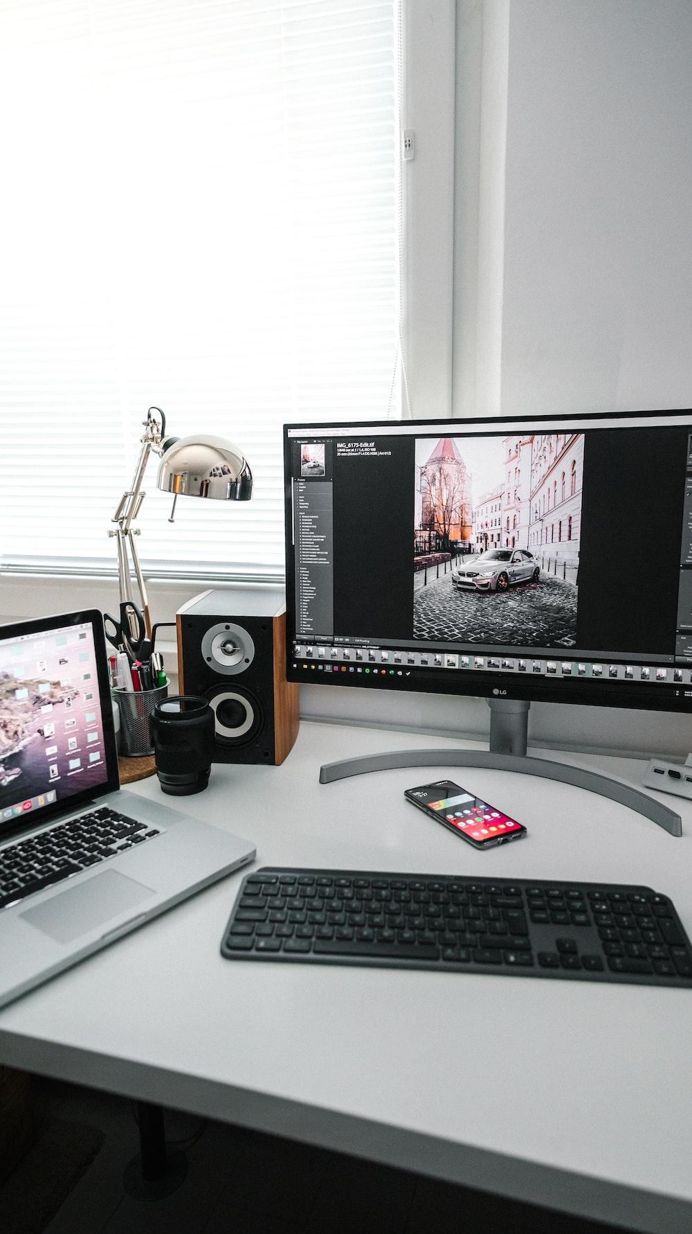 black flat screen computer monitor beside black computer keyboard and black computer speakers