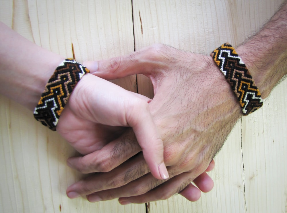 person wearing black and gold bracelet
