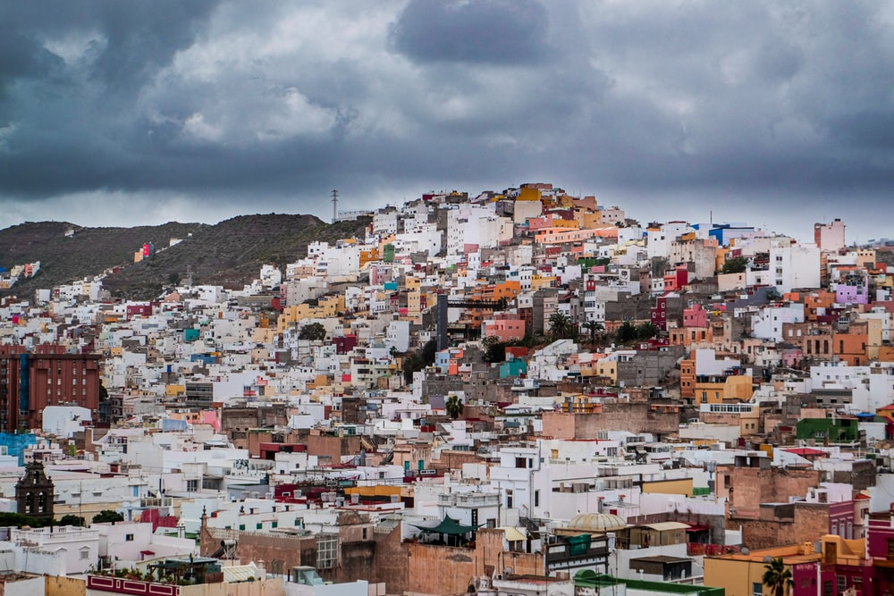 white and brown houses on hill under white clouds during daytime