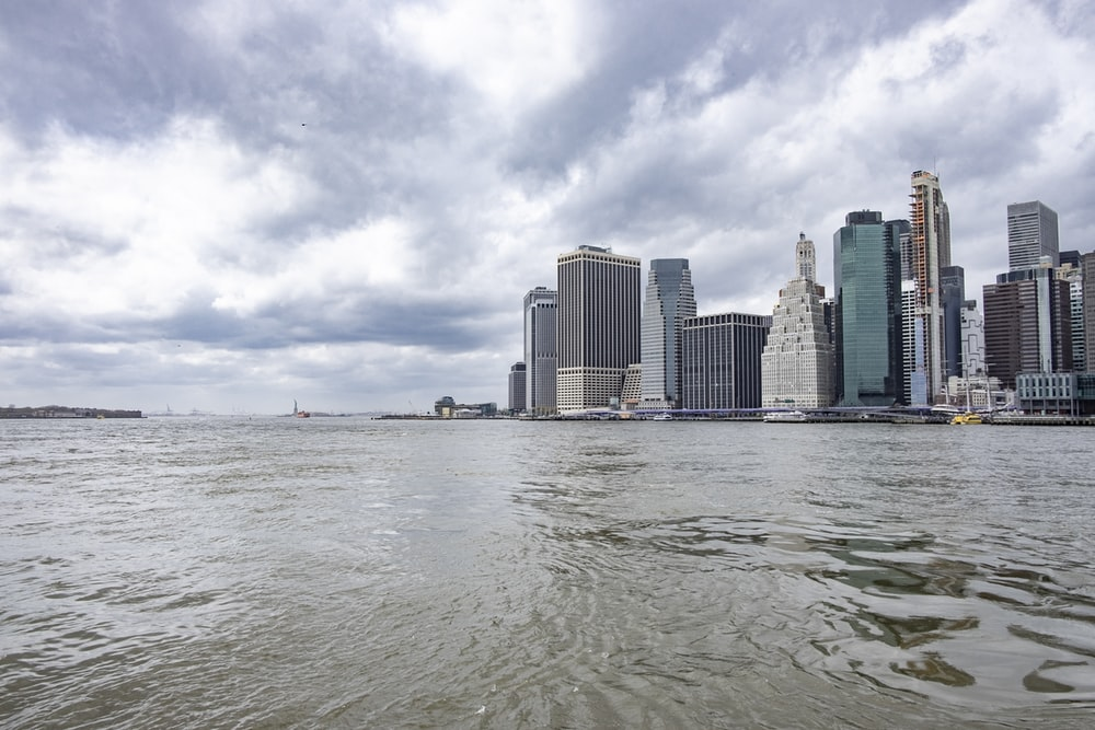body of water near city buildings under white clouds and blue sky during daytime