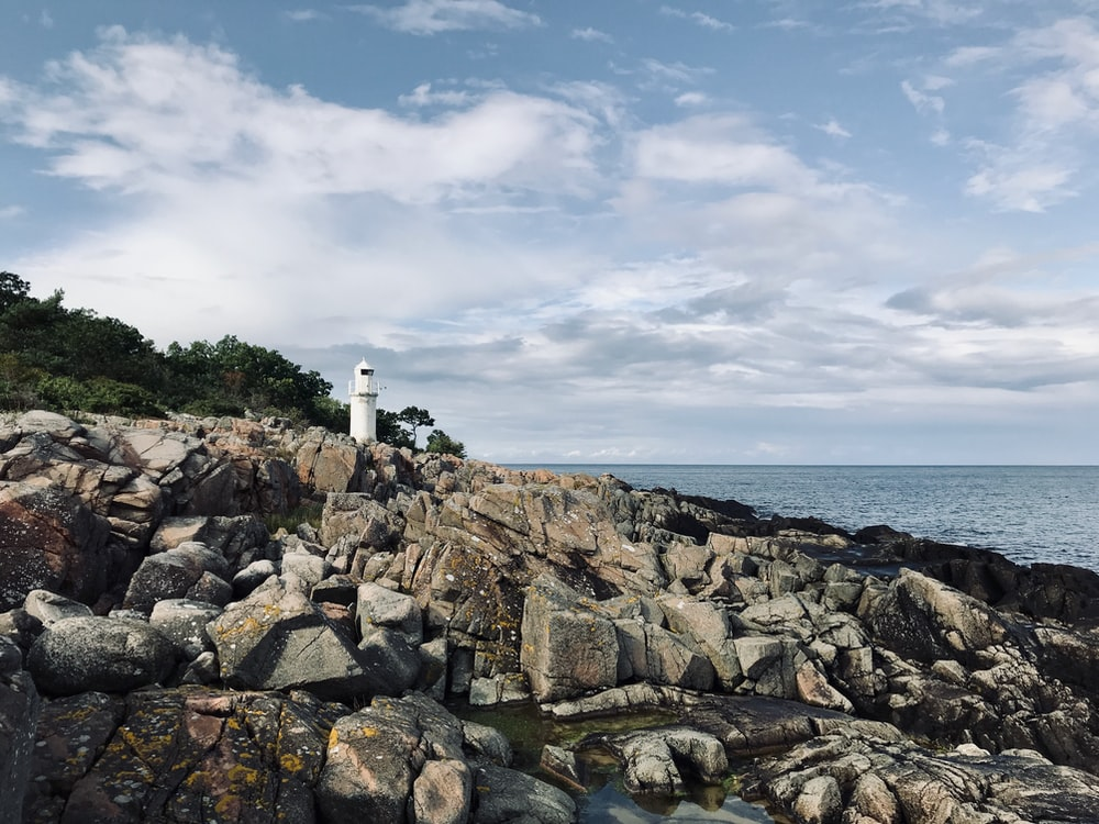 white lighthouse on rocky shore under cloudy sky during daytime