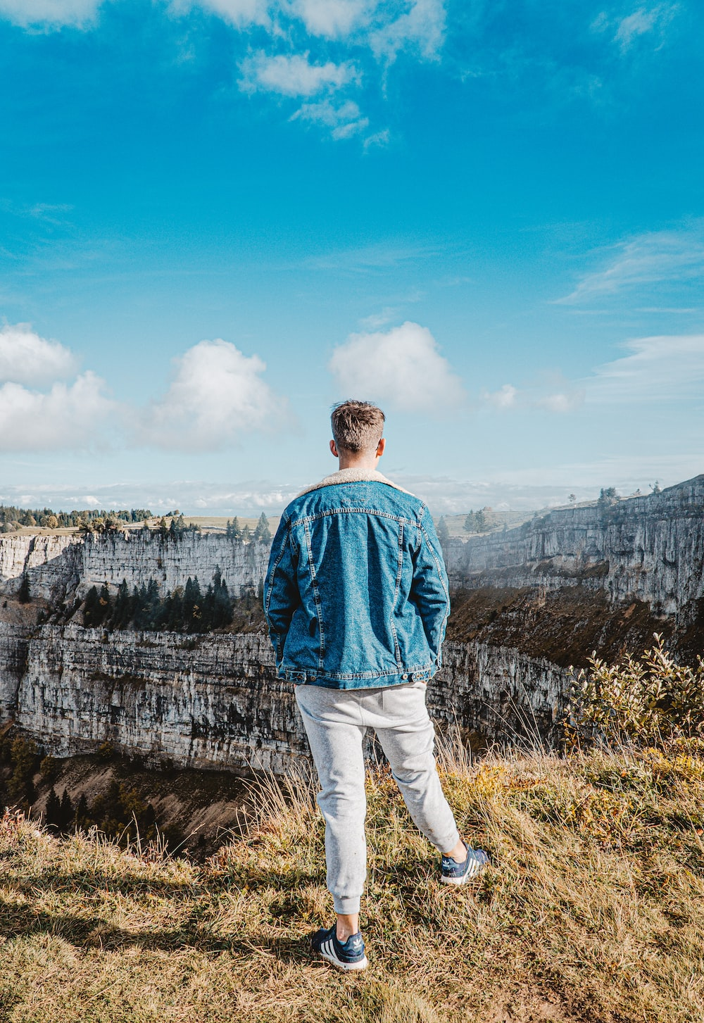 man in blue dress shirt standing on cliff during daytime