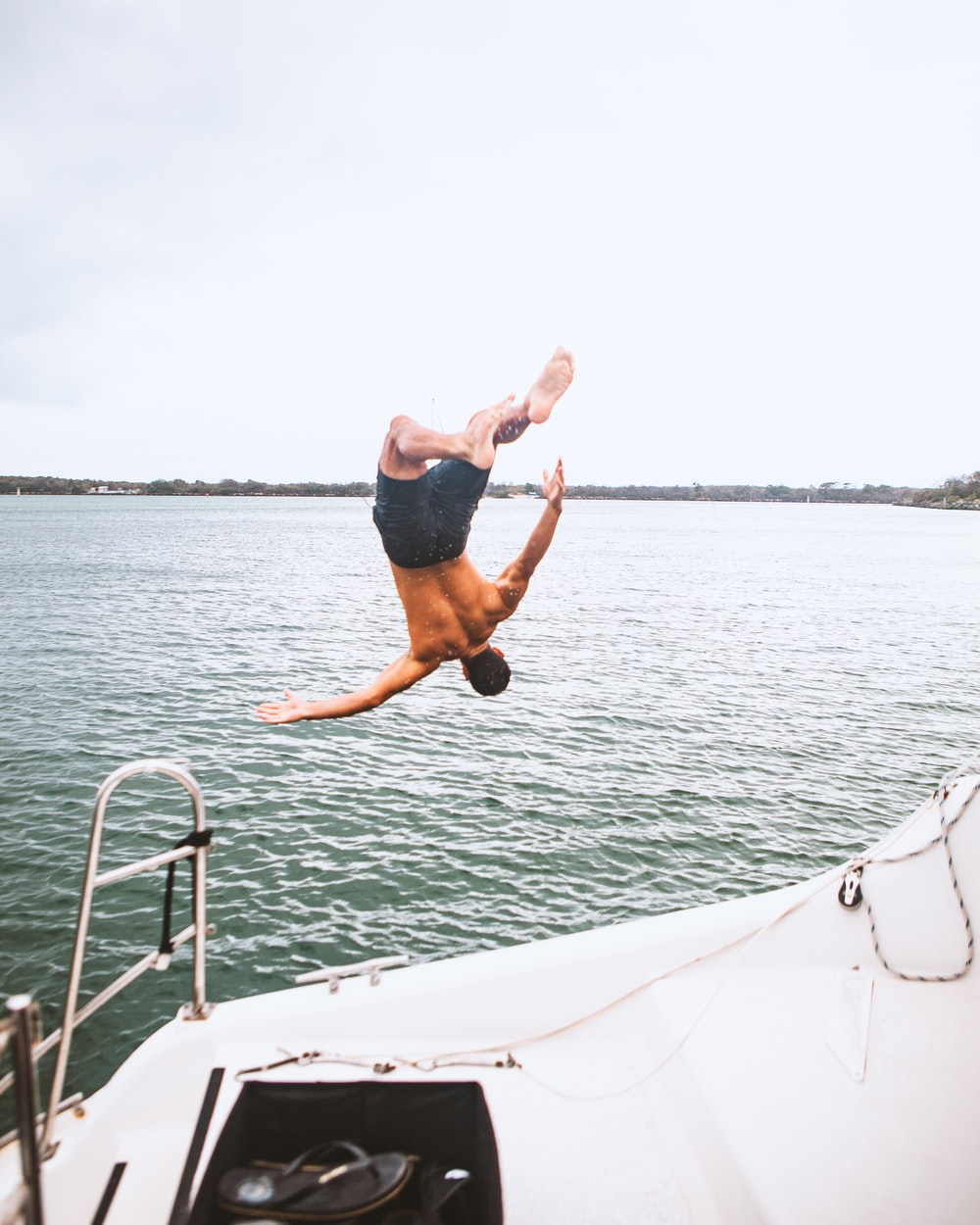 man in black shorts jumping on white boat during daytime