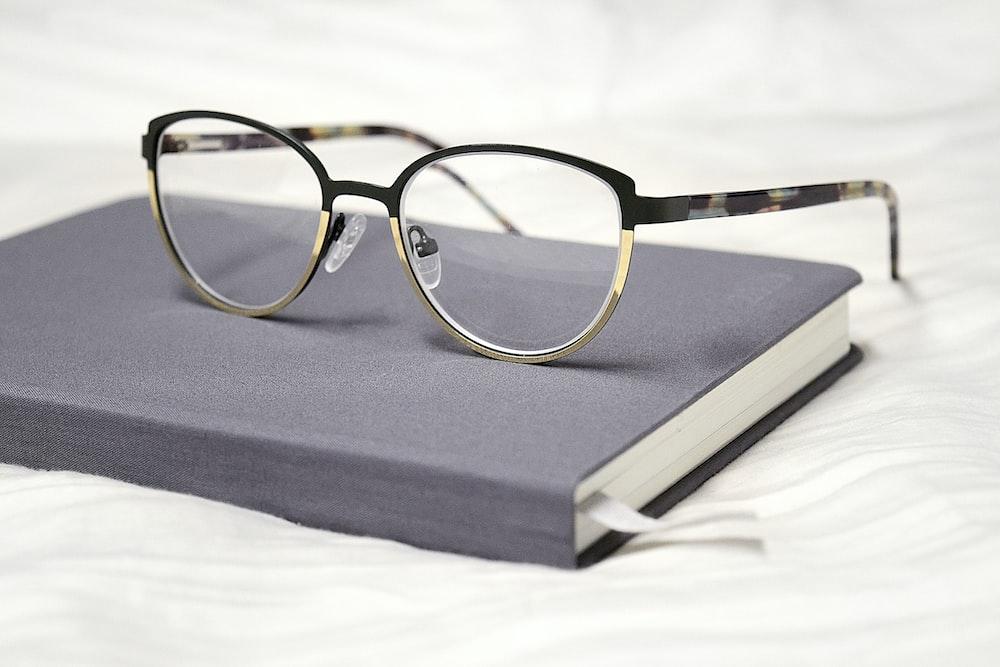 black framed eyeglasses on black book