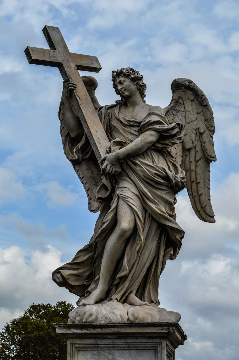 angel statue under white clouds during daytime