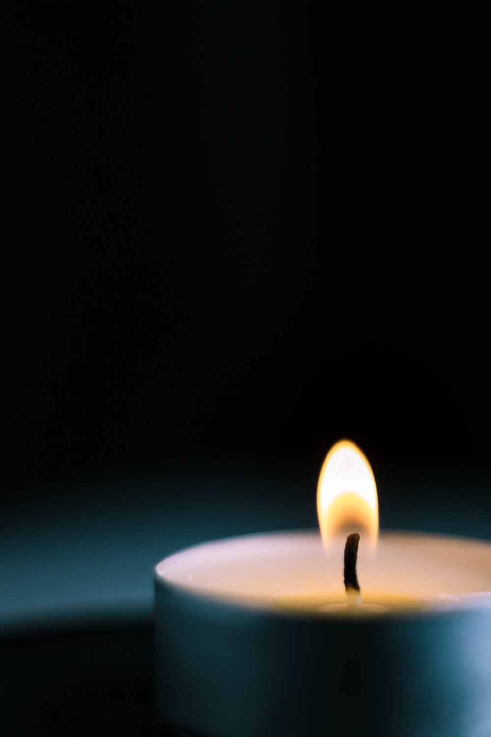 white candle with fire in dark room