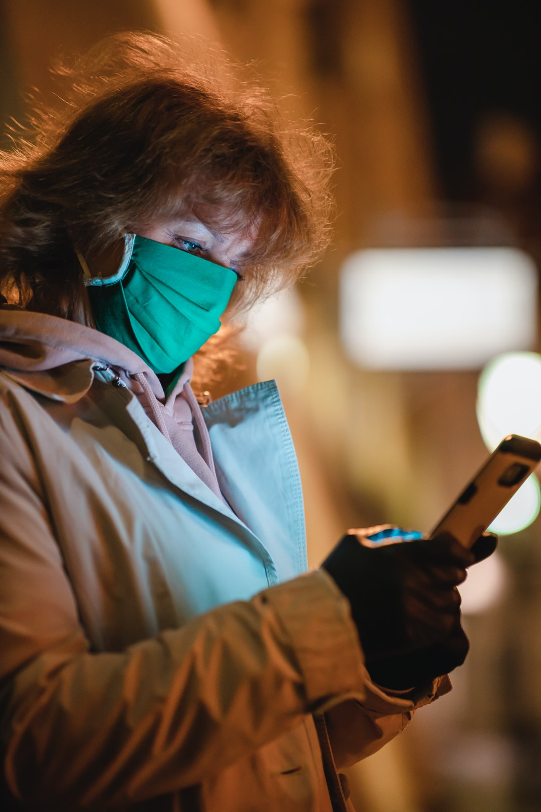 Woman in green face mask using smartphone at night during the COVID-19 pandemy. Warsaw, Old Town, Poland