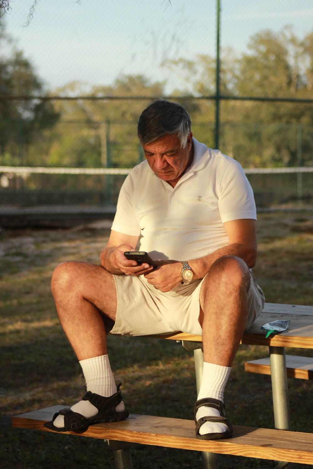 man in white polo shirt and black shorts sitting on brown wooden bench