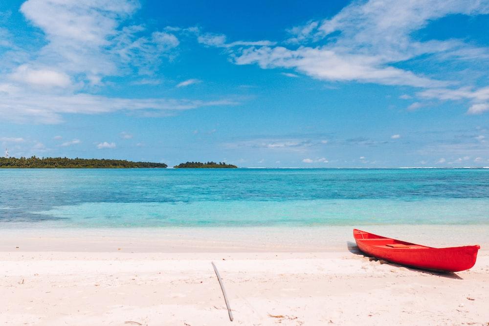 red kayak on beach shore during daytime