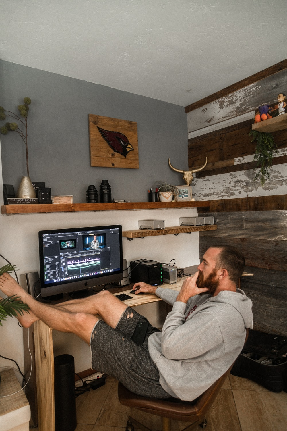 man in gray shirt and black shorts sitting on chair using laptop computer