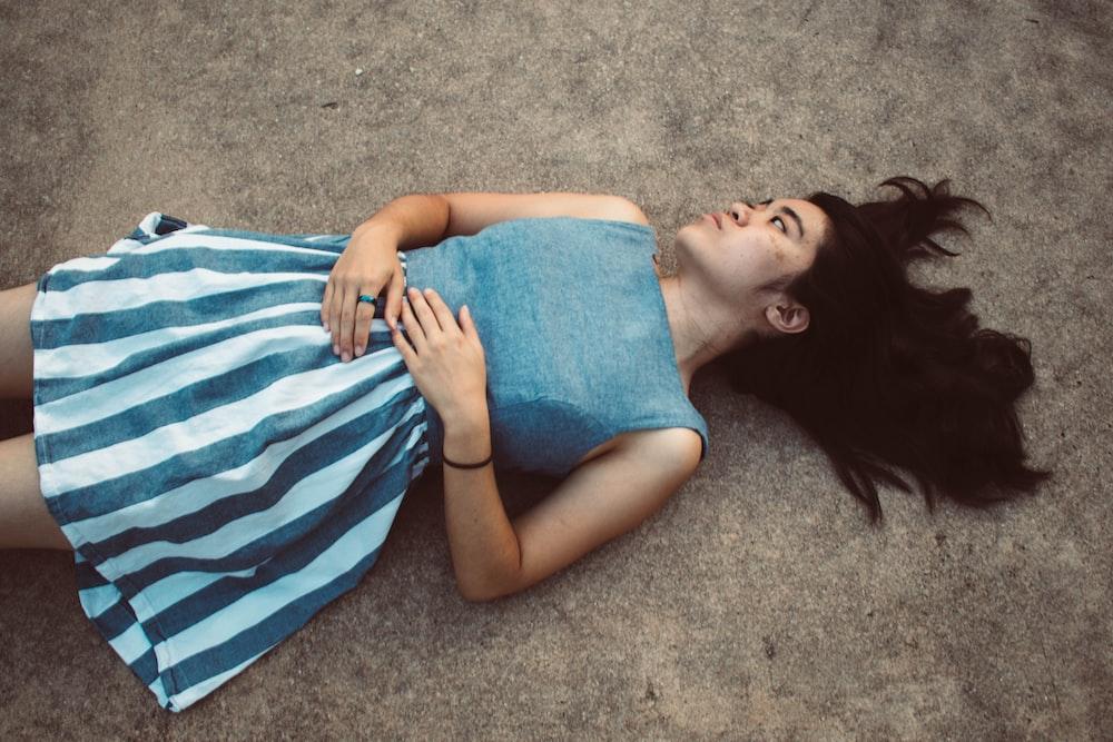 woman in blue tank top lying on gray carpet