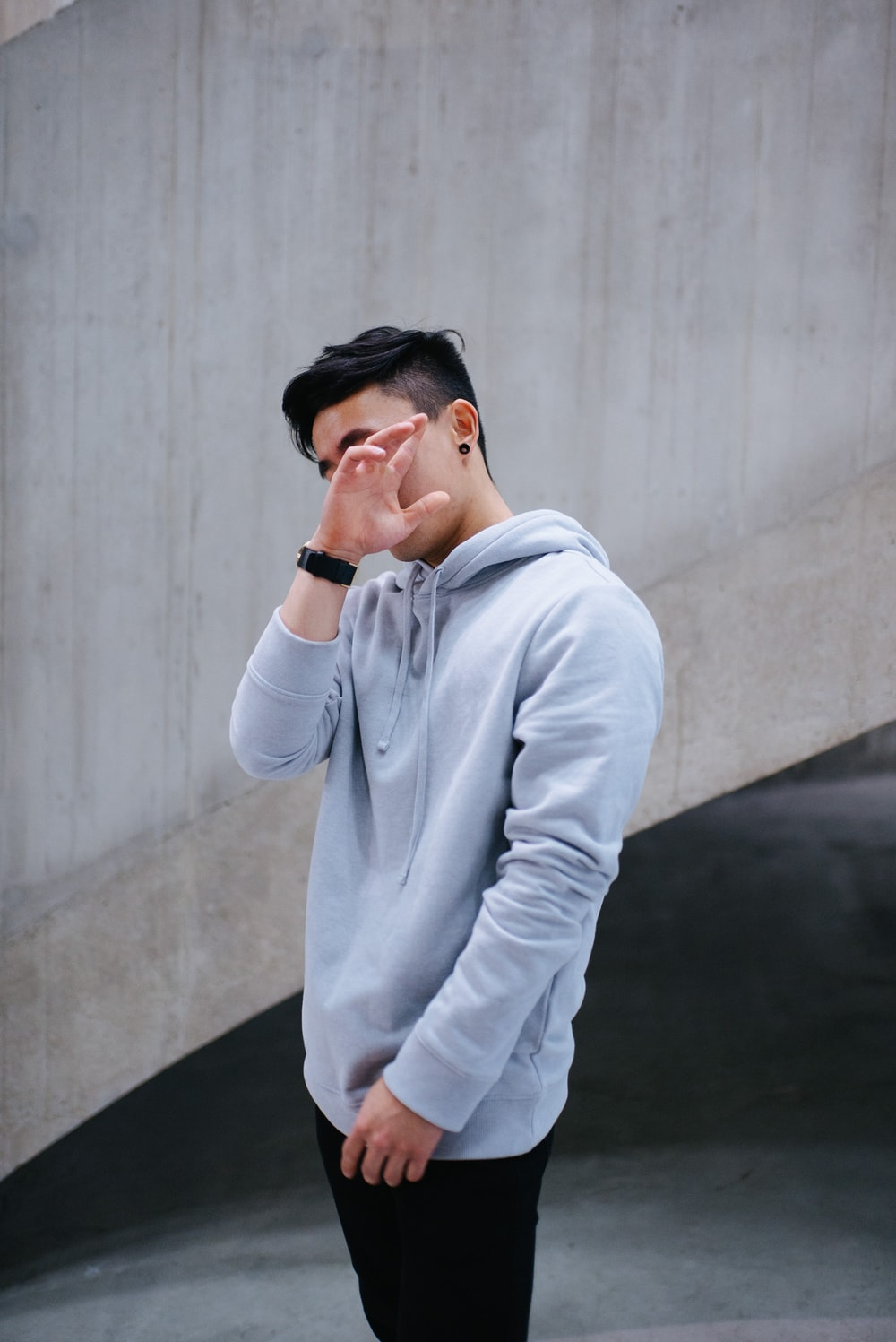 man in gray hoodie standing and leaning on wall