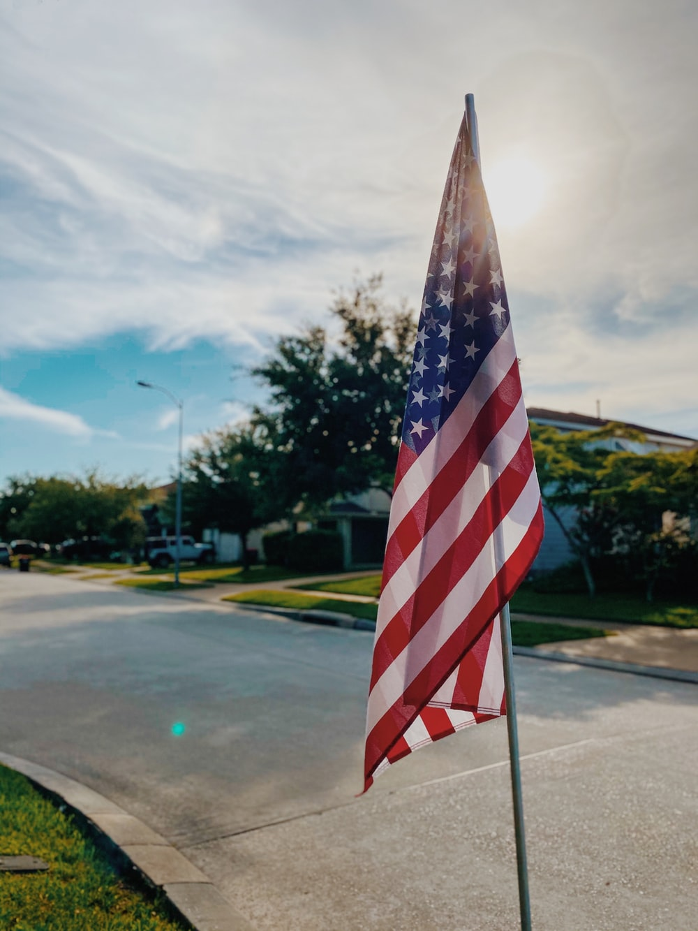 us a flag on gray asphalt road during daytime