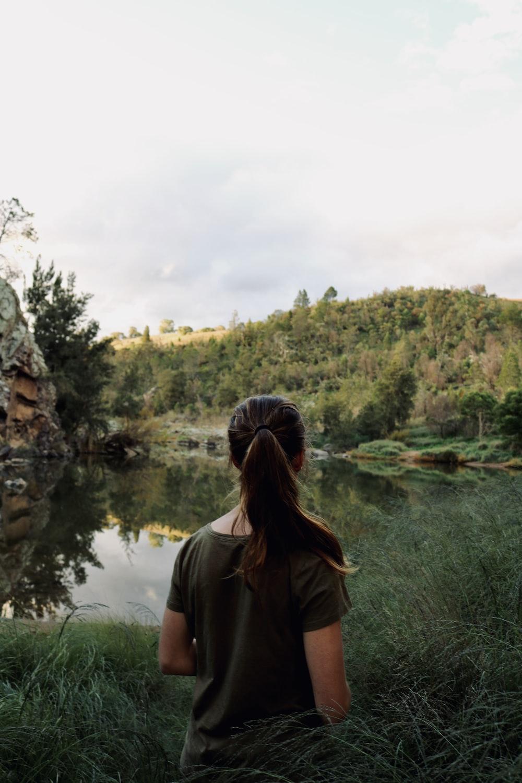 woman in brown shirt standing near lake during daytime