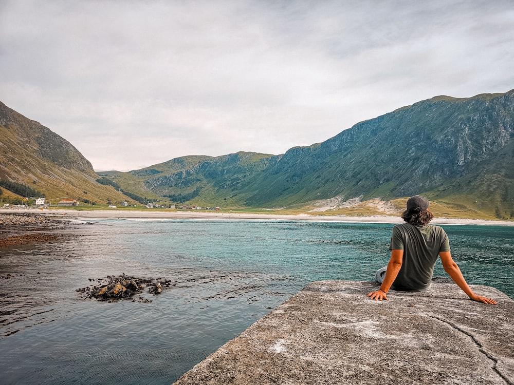 man in black t-shirt sitting on rock near body of water during daytime
