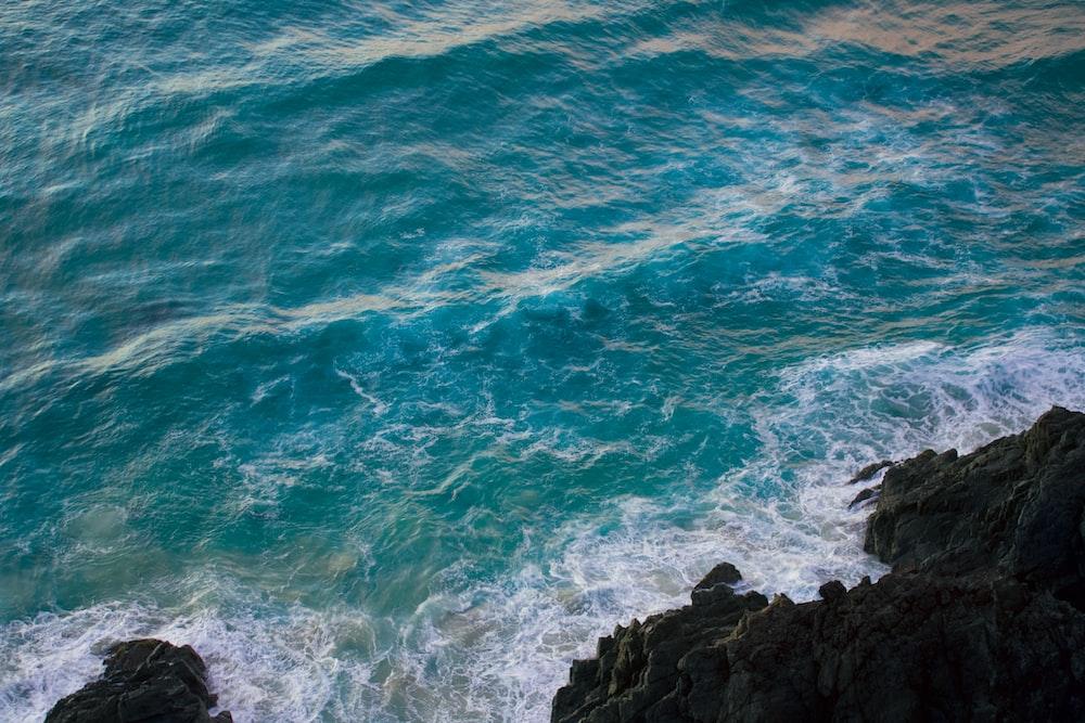 blue ocean waves crashing on black rock formation during daytime