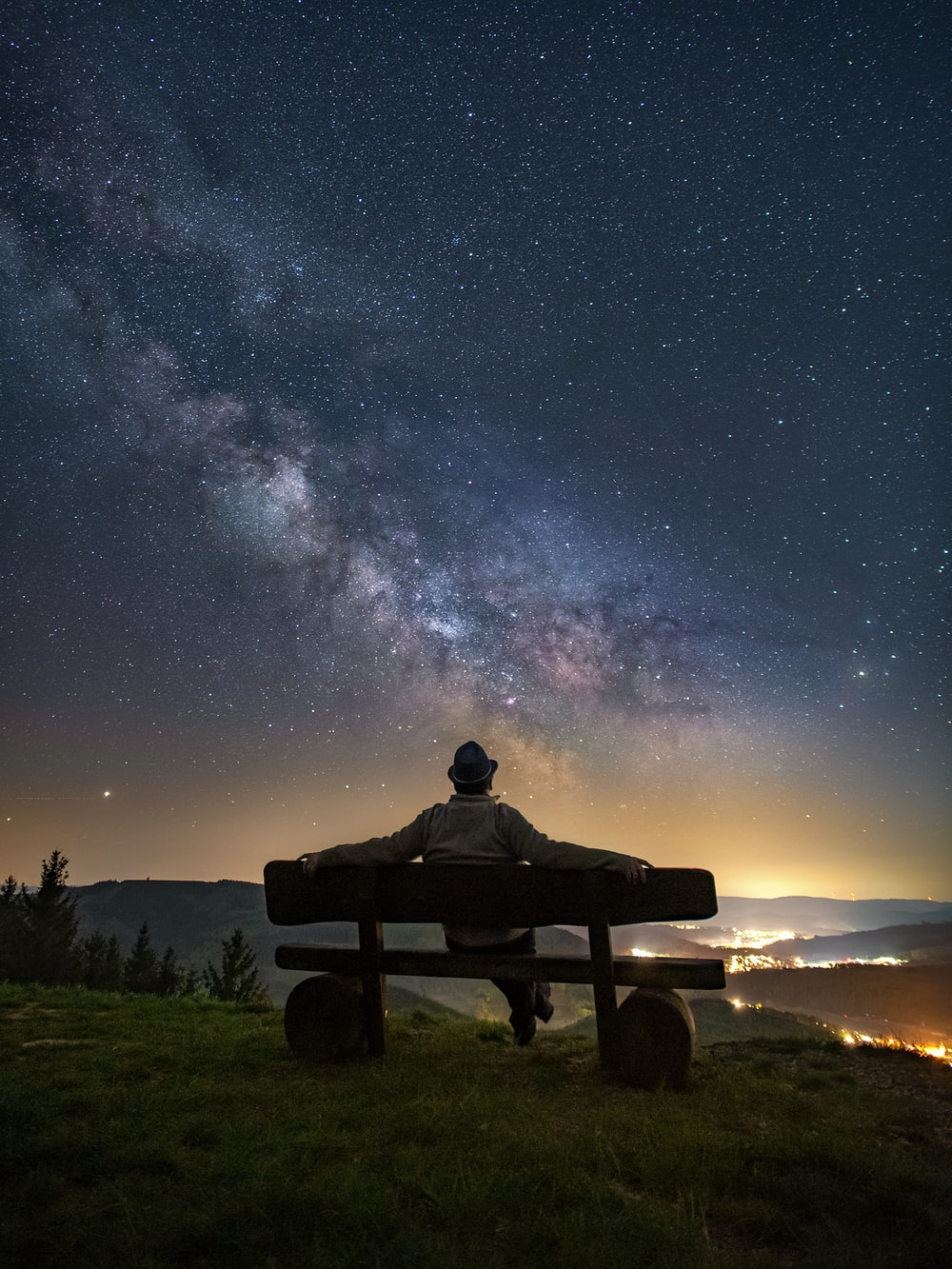 man and woman sitting on bench under starry night