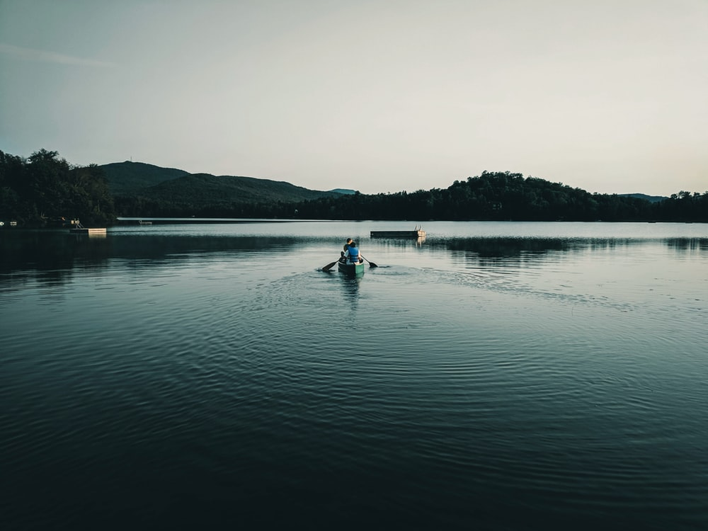 2 people riding on boat on lake during daytime