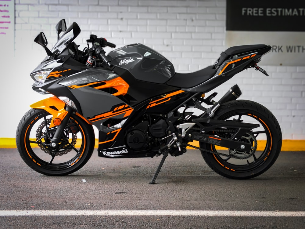 black and orange sports bike parked beside white wall