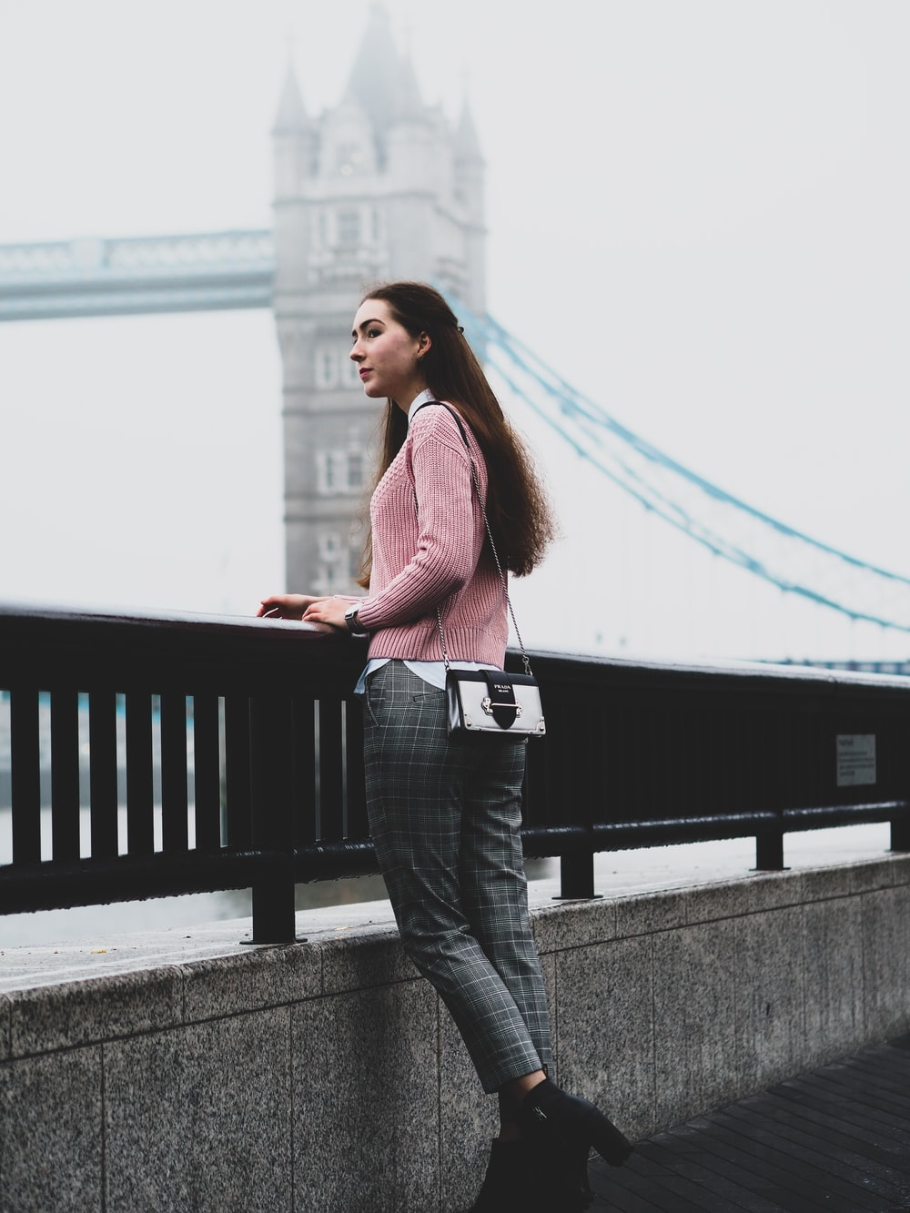 woman in pink long sleeve shirt and blue denim jeans standing on bridge during daytime