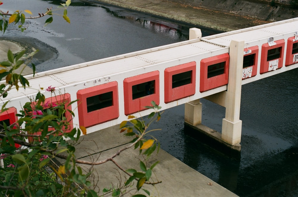 white and red concrete building beside body of water