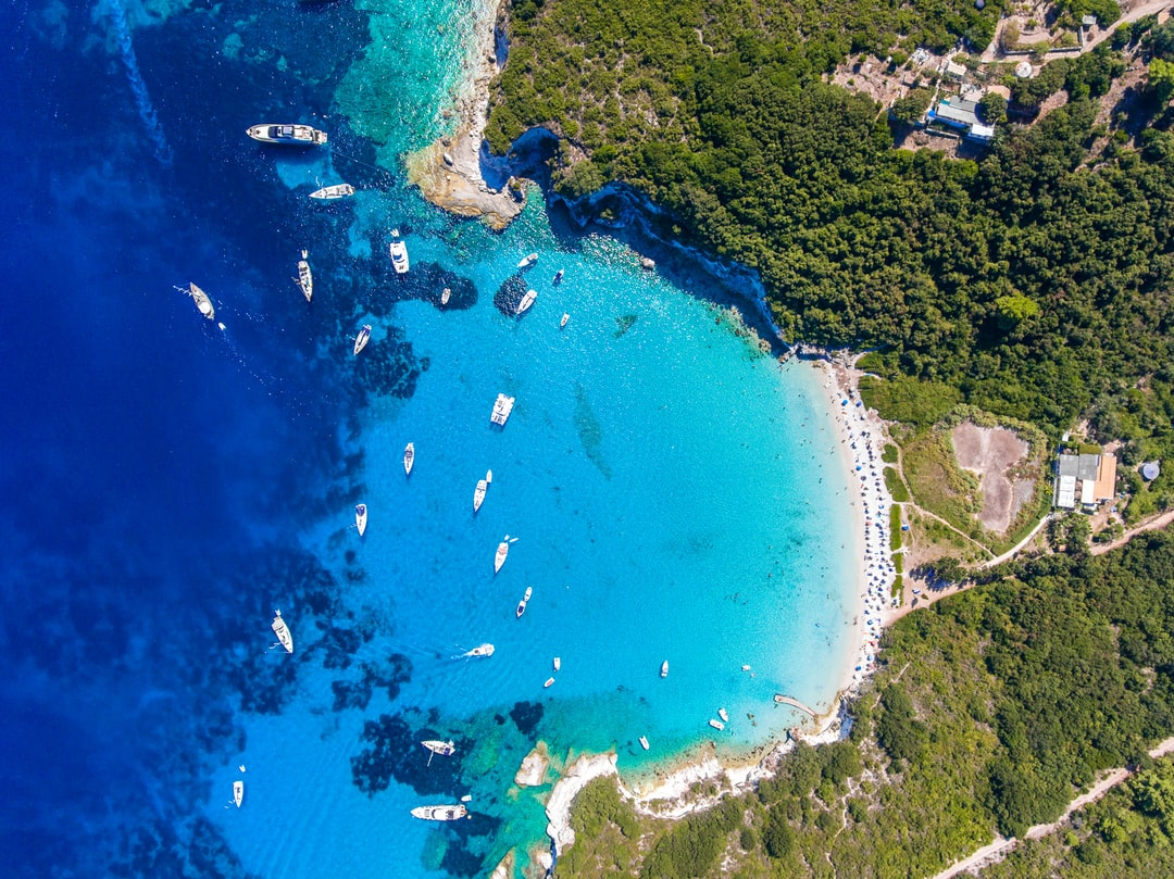 Antipaxos Island, Greece, with sandy beach, people swimming and yachts docked in the ethereal clear blue waters of the Ioanian island near Corfu