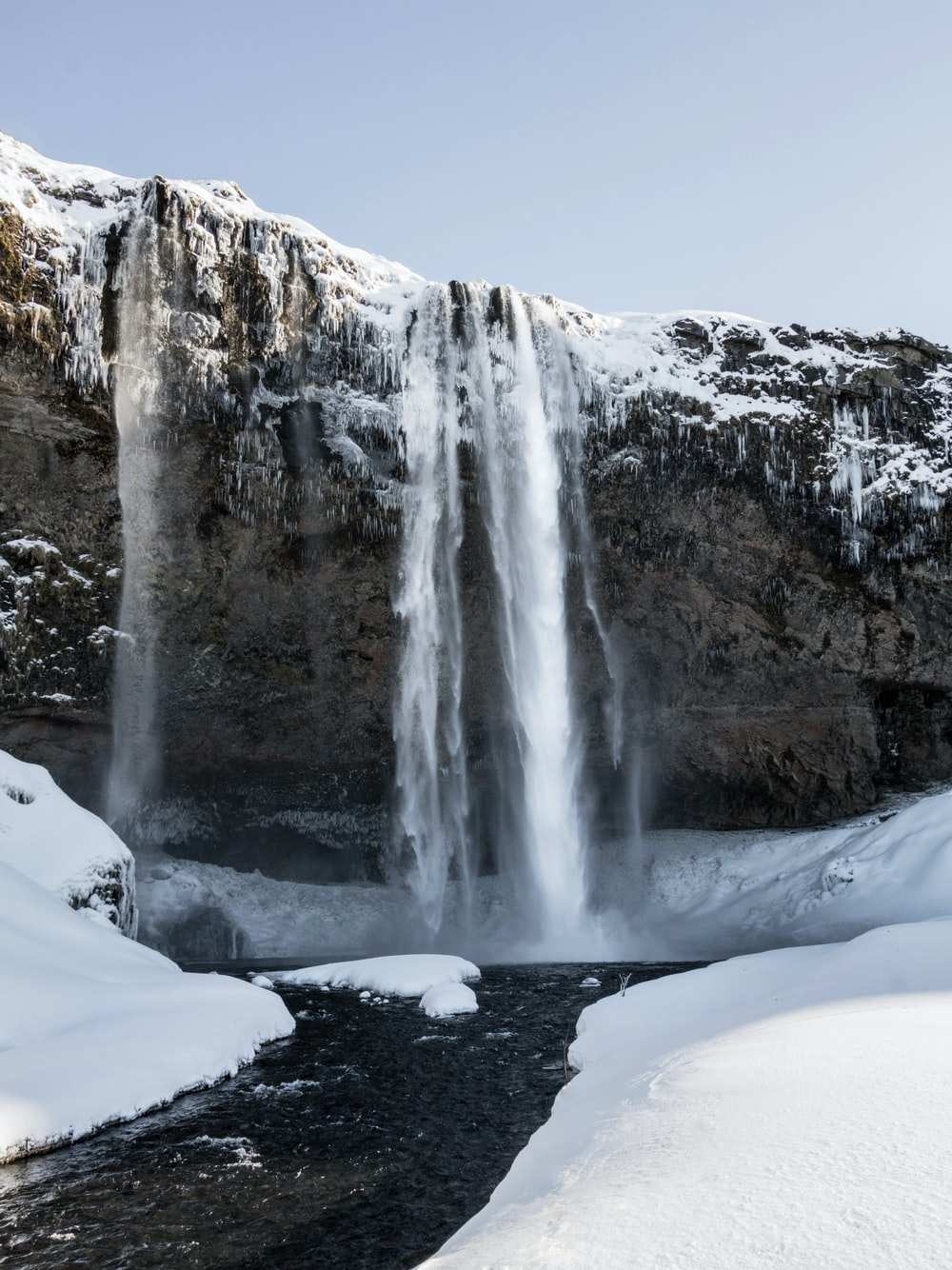 waterfalls on snow covered ground during daytime