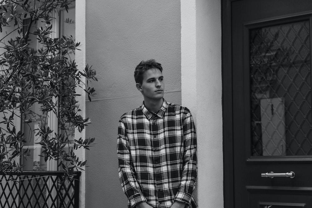 man in plaid dress shirt standing beside wall