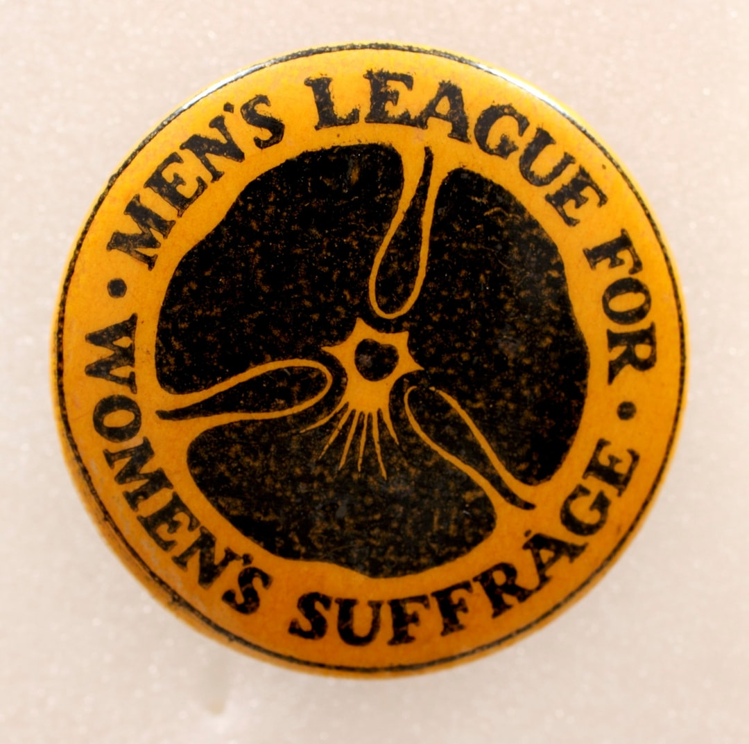 Suffrage Campaigning: Men's League for Women's Suffrage, 1907-1918. Badge, paper, metal, round, produced by the Men's League for Women's Suffrage, yellow ground, printed with black inscription: 'Men's League for Women's Suffrage', paper covered with plastic, over metal base. TWL.2004.608