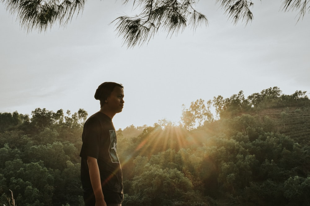 man in black crew neck t-shirt standing near green trees during daytime