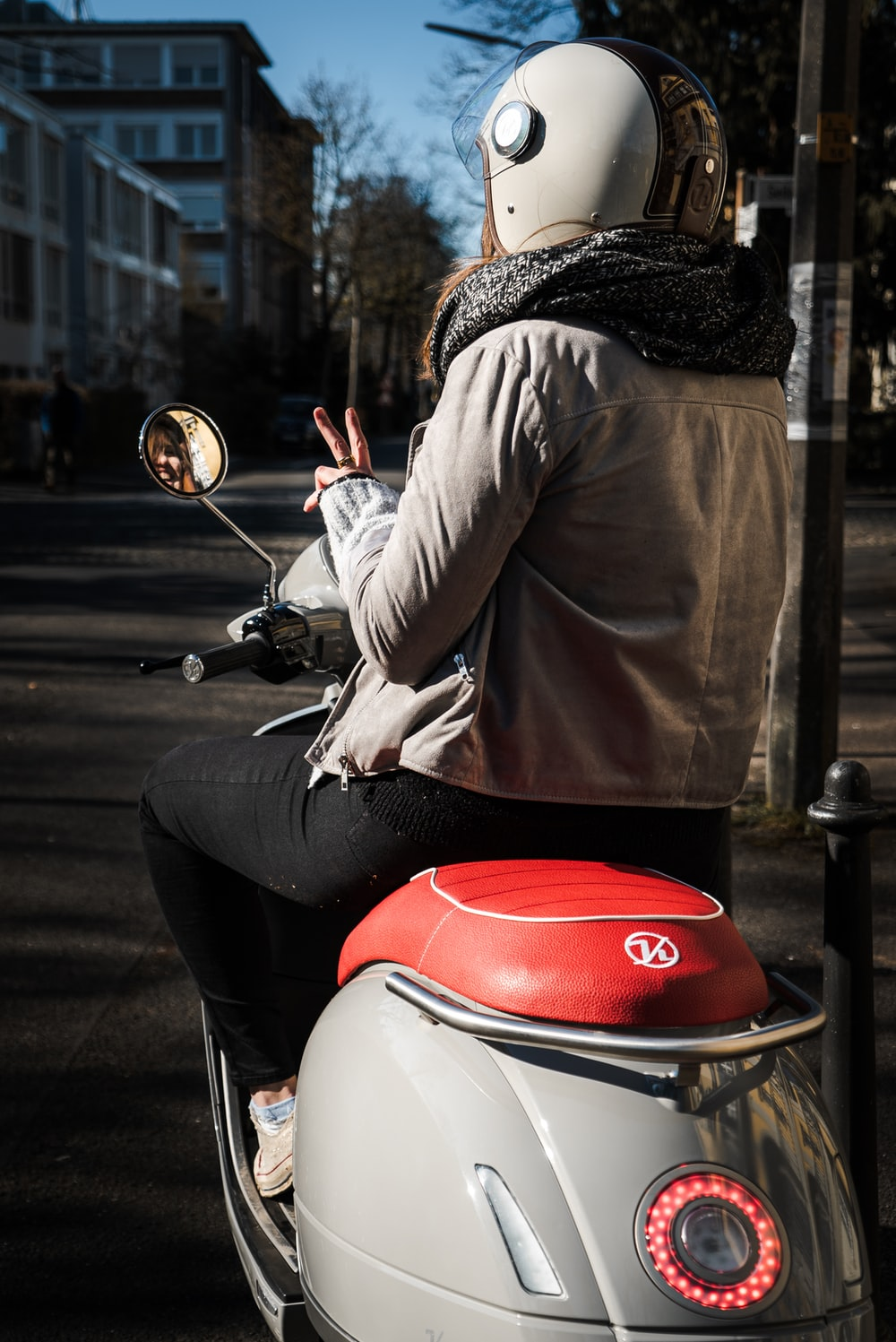 person in brown long sleeve shirt riding on red and white motor scooter during daytime