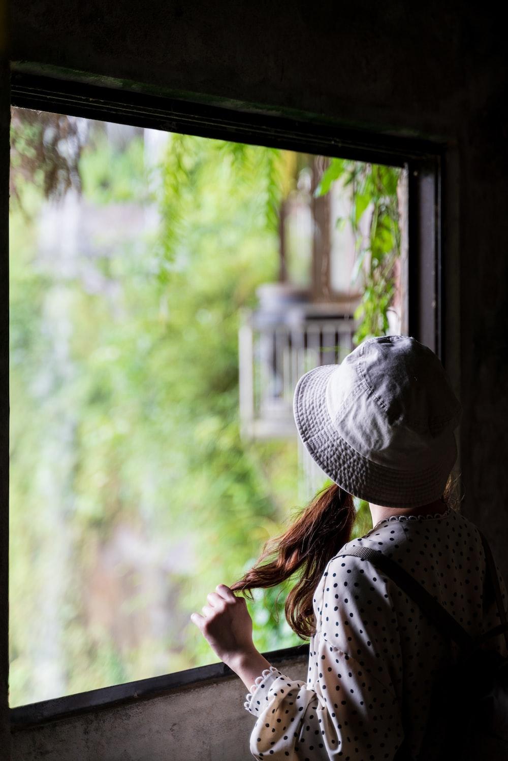woman in white and black polka dot shirt standing near window