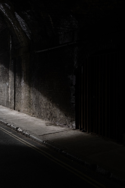 black wooden door beside gray concrete wall
