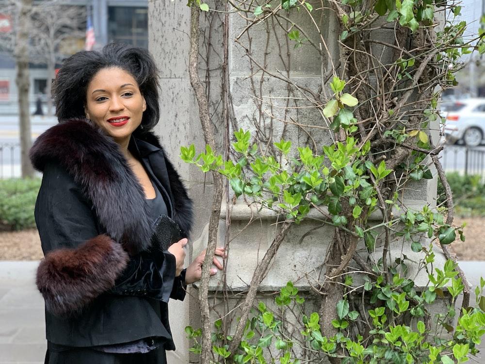 woman in black coat standing beside green plant