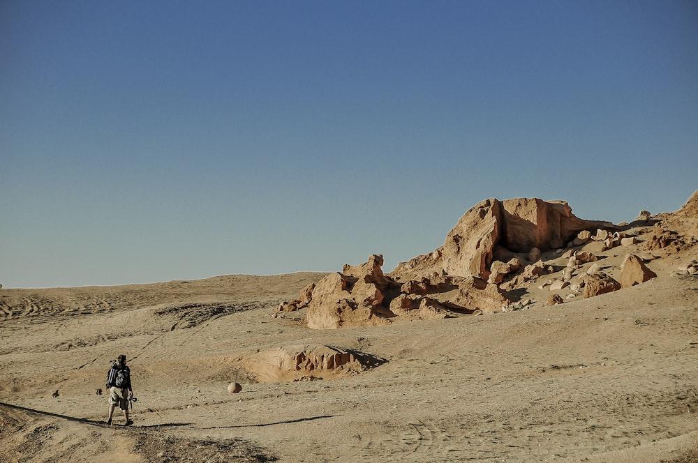 man in black jacket walking on brown sand during daytime