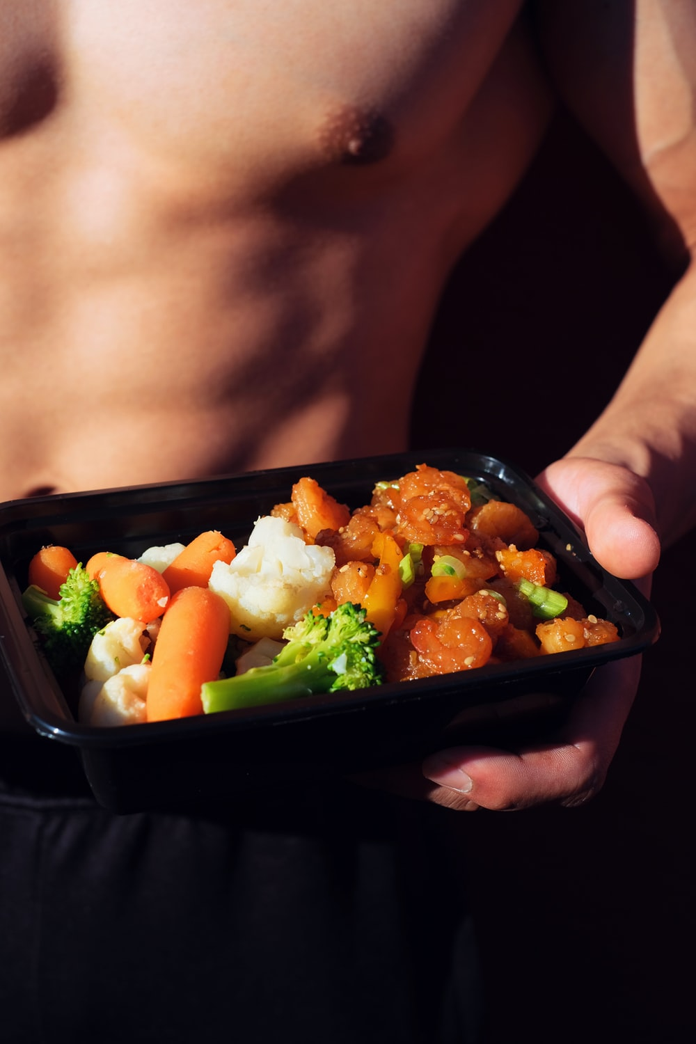 person holding black plastic container with food
