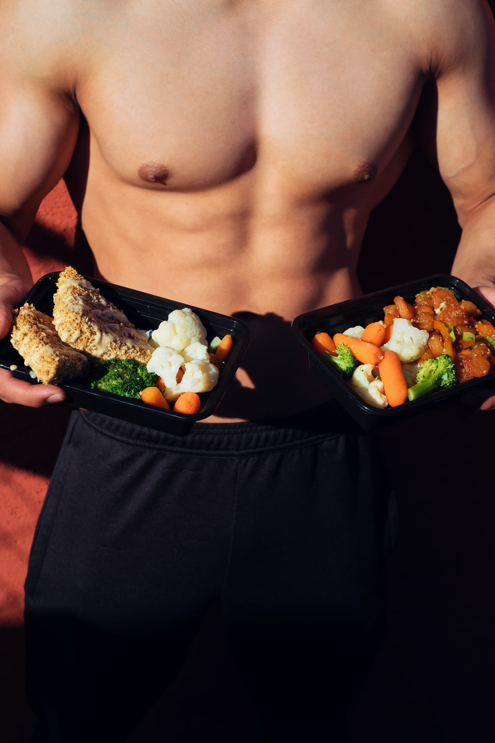 topless man in black shorts holding cooked food