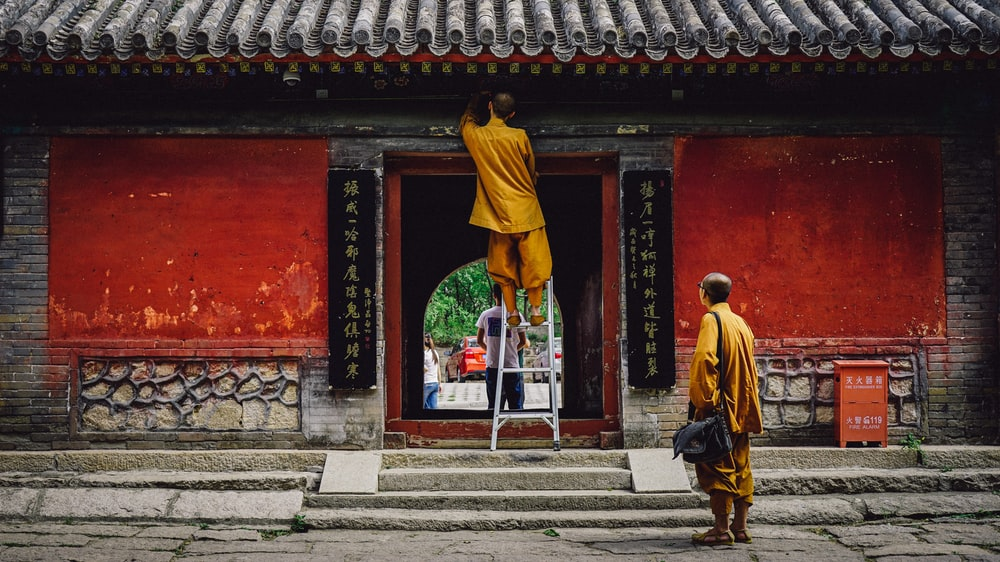 man in yellow robe walking on gray concrete stairs