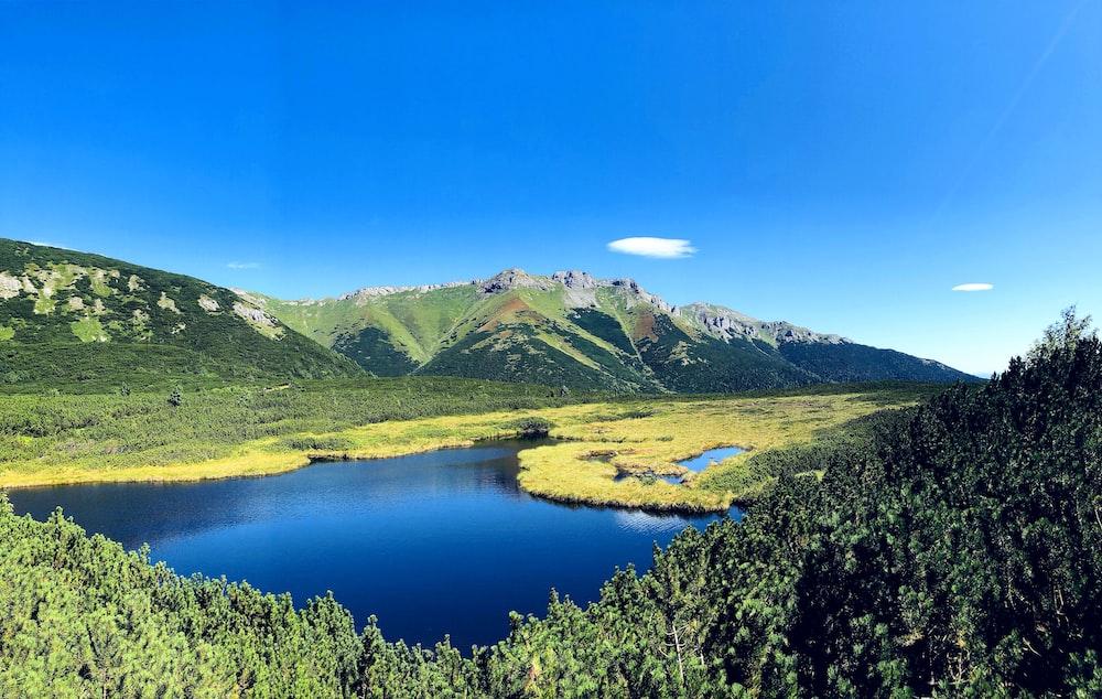 green mountains near lake under blue sky during daytime