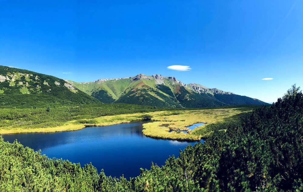 green mountains near lake under blue sky during daytime