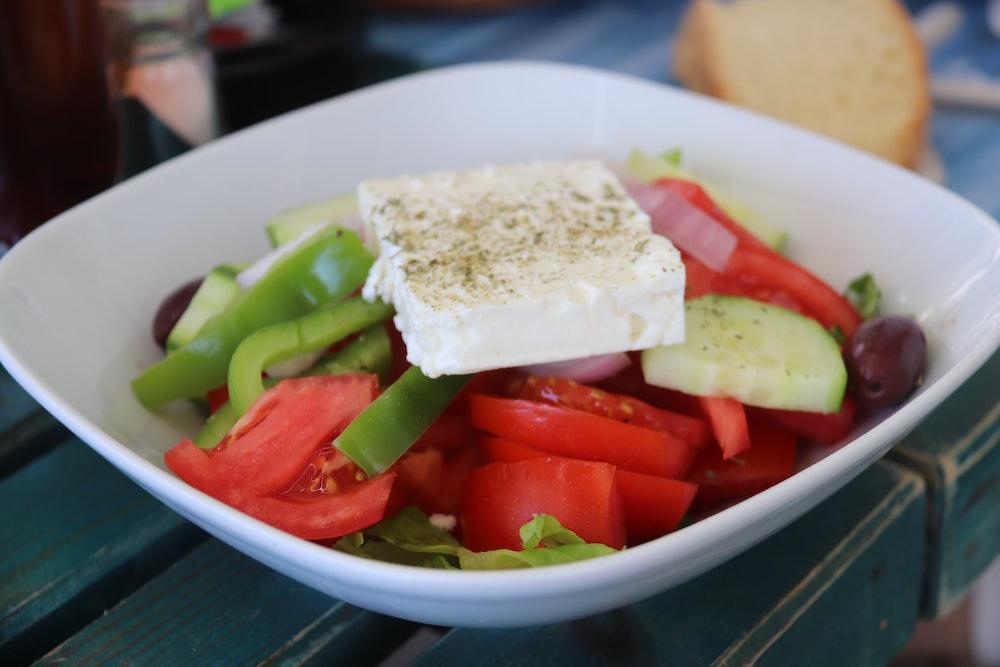sliced tomato and green vegetable on white ceramic bowl