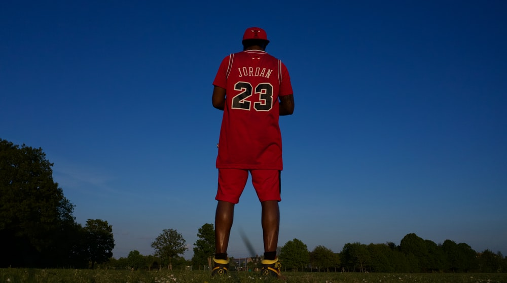 man in red and white jersey shirt and shorts standing on green grass field during daytime