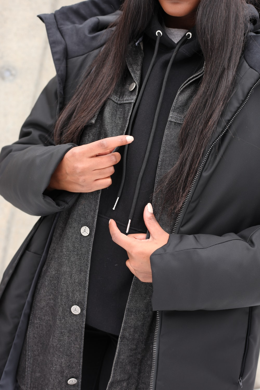 woman in black coat holding her chin